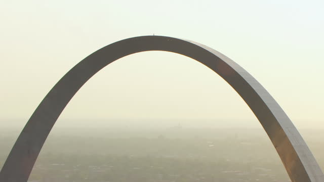 ms aerial zo shot of top of gateway arch to reveal downtown in back side during sunset / st louis, missouri, united states - arch architectural feature stock videos and b-roll footage