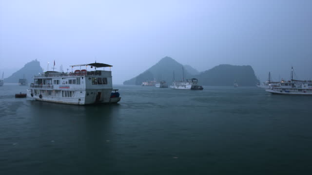 ms t/l pov shot of tourist boats gently float at anchor in grey daybreak with darker island shapes in back side / ha long bay, vietnam - flotilla stock videos & royalty-free footage