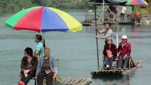 ms shot of tourist travelling from traditional boats at river / close to li river, guangxi, china - li river stock videos & royalty-free footage