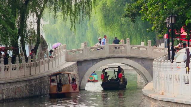 ms shot of tourists enjoying boat ride and yingding bridge at houhai lakes / beijing, china - arch stock videos & royalty-free footage