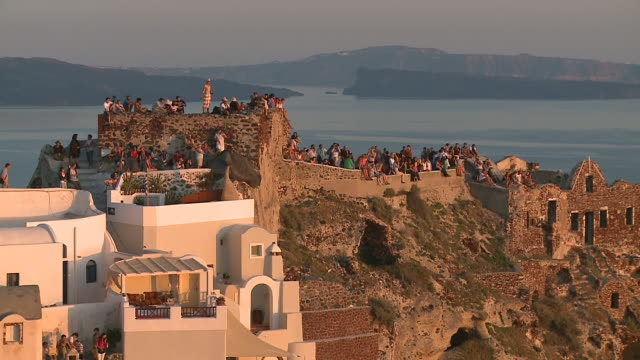ms shot of tourists on hill at sun settin in village oia / santorini, cyclades, greece - oia santorini stock videos & royalty-free footage