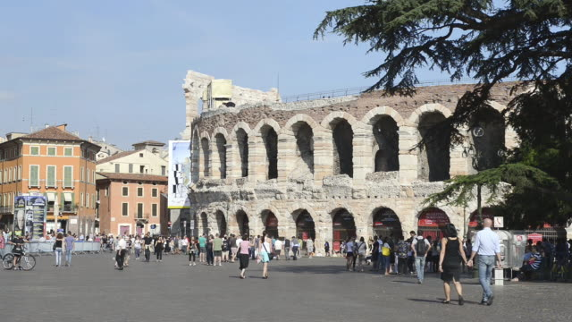 ms shot of tourists roaming in front of arena di verona at piazza bra / verona, veneto, italy - vita cittadina video stock e b–roll