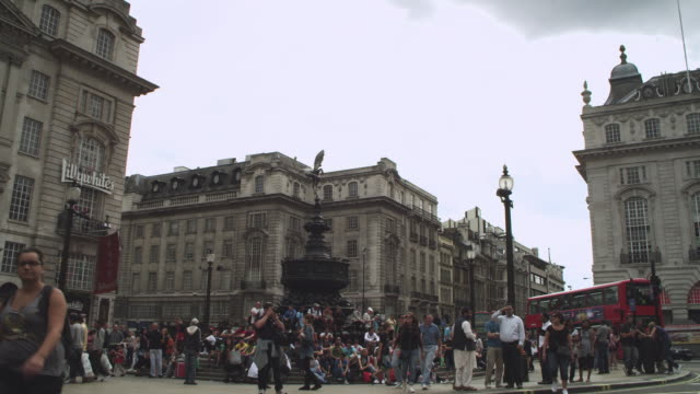 ms shot of tourists sit under eros statue with traffic  / london, england - piccadilly stock videos and b-roll footage