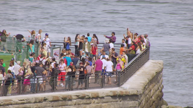 ms aerial shot of tourists walking on pathway at base of statue of liberty on liberty island / new jersey, united states - sockel stock-videos und b-roll-filmmaterial