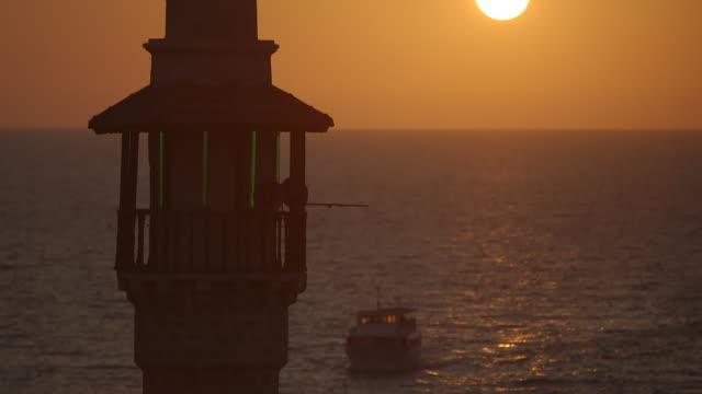 ms tu shot of tower and boat on mediterranean sea at sunset / jaffa, tel, aviv israel - jaffa stock videos & royalty-free footage