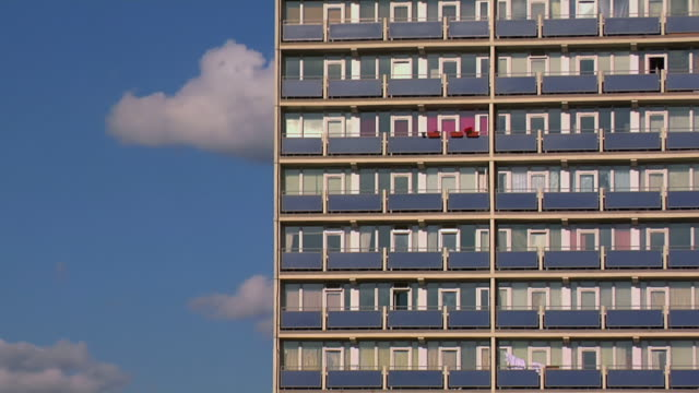 ms t/l shot of tower block in east london against blue sky with rolling clouds / london, united kingdom  - 集合住宅点の映像素材/bロール