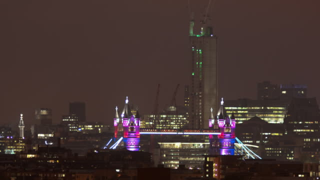 ms t/l pan shot of tower bridge illuminated at night with draw bridge raising and lowering / london, united kingdom - lowering stock videos & royalty-free footage