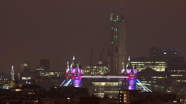 stockvideo's en b-roll-footage met ms t/l pan shot of tower bridge illuminated at night with draw bridge raising and lowering / london, united kingdom - laten zakken