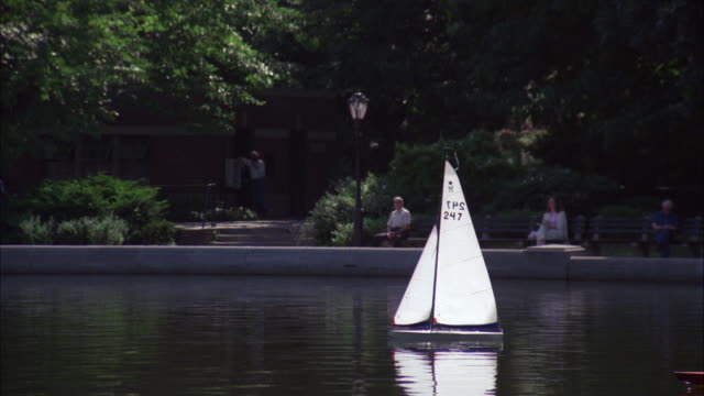stockvideo's en b-roll-footage met ms ts shot of toy boats on lake in central park - 1983