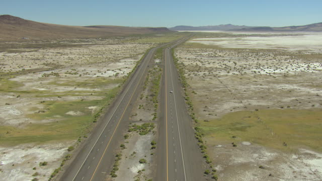 ws aerial shot of tracking interstate 80 in lyon county through dry lake bed on sunny day / nevada, united states - lake bed stock videos & royalty-free footage