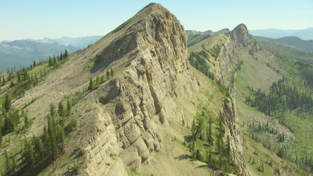MS AERIAL Shot of tracking ridge with Chinese Wall in Bob Marshall Wilderness area / Montana, United States