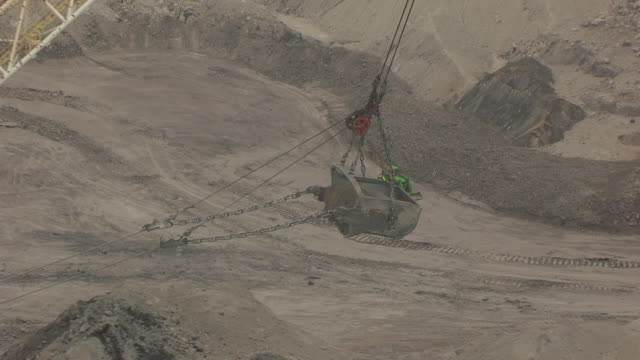 CU AERIAL TS DS Shot of Tractor dumping load of dirt to side of coal mine to tractor at North Antelope Rochelle Mine / Wyoming, United States