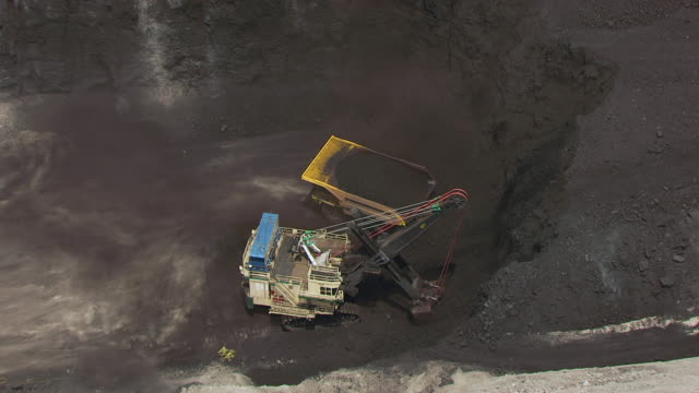CU AERIAL ZO Shot of Tractor dumping loading of dirt in truck in open trench and North Antelope Rochelle Mine / Wyoming, United States