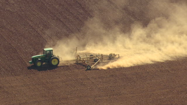 MS AERIAL TS Shot of tractor grading dirt on farm field in northwest Alabama / Alabama, United States