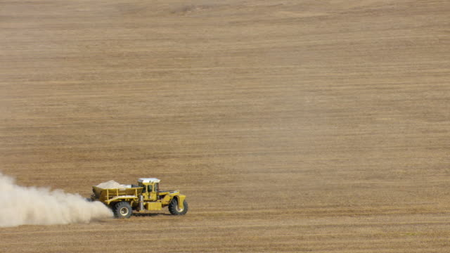 ms aerial ts shot of tractor raising dust while plowing field on farm in colbert county / alabama, united states - trattore video stock e b–roll