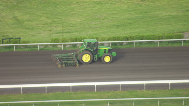 ms aerial ts shot of tractor smoothing track and keeneland track / versailles, kentucky, united states - 修理する点の映像素材/bロール