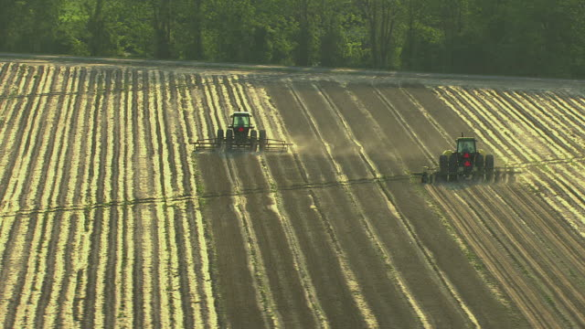 ms aerial shot of tractors tilling cotton farm in sharkey county with sunlight / mississippi, united states - tractor stock videos & royalty-free footage