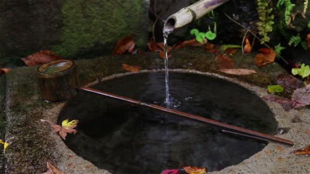 vídeos de stock e filmes b-roll de ms shot of traditional fountain at small mountainside shrine in minakami rural area - bambu material