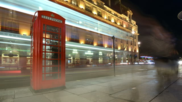ms zi t/l shot of traditional red phone box on picadilly street with ritz hotel in commuters and traffic pass rapidly / london, greater london, united kingdom - 電話ボックス点の映像素材/bロール