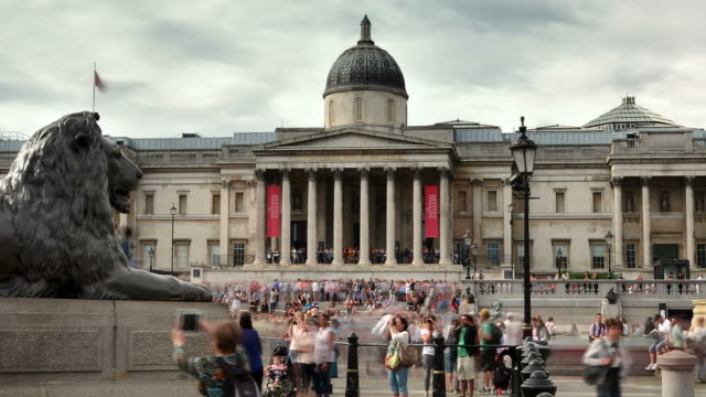 ms pan t/l shot of trafalgar square central london, sir edwin landseers lion sculptures and national gallery in back side visitors moving and cloudy sun comes out / london, greater london, united kingdom - greater london video stock e b–roll