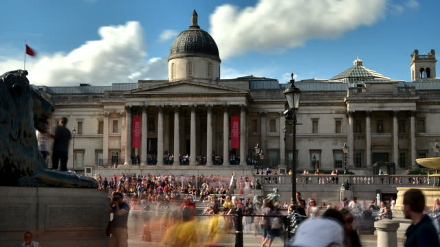 MS PAN T/L Shot of Trafalgar Square Central London, Sir Edwin Landseers lion sculptures and national gallery with visitors moving and sunny white clouds / London, Greater London, United Kingdomon blue sky