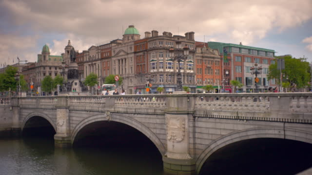 shot of traffic and pedestrians crossing over a bridge over the river liffey in dublin, ireland on a summer day - arch bridge stock videos and b-roll footage