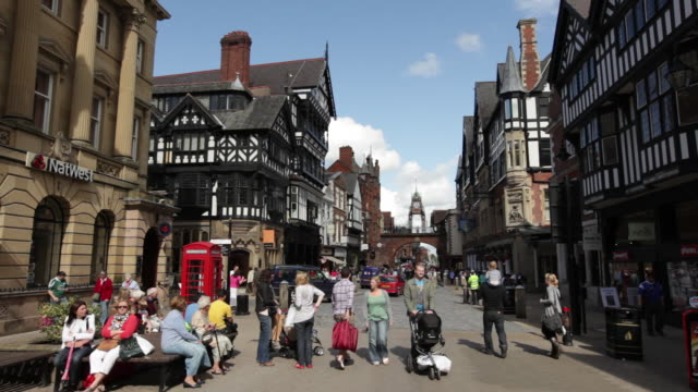 ms shot of traffic and pedestrians moving on street / chester, england - chester england stock videos and b-roll footage