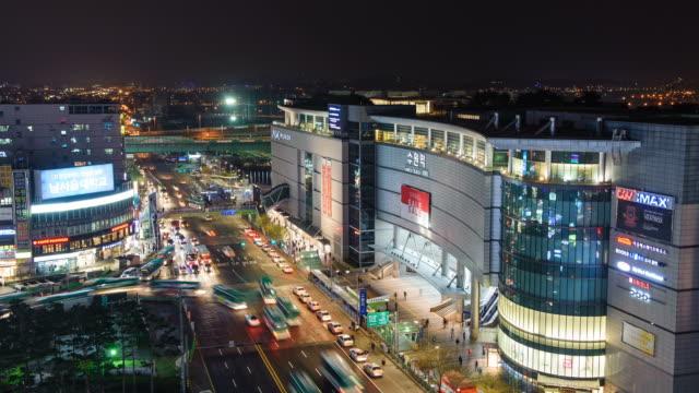 ms t/l shot of traffic and stores near suwon station area at night / suwon, gyeonggi-do, south korea  - suwon stock videos and b-roll footage