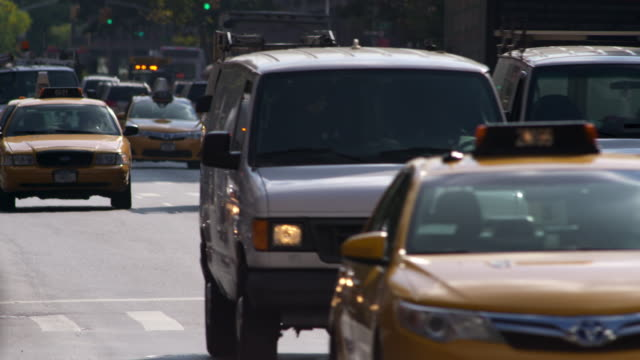 shot of traffic coming towards the camera on a busy new york city street. a man on a bike signals and turns out of frame - yellow taxi video stock e b–roll