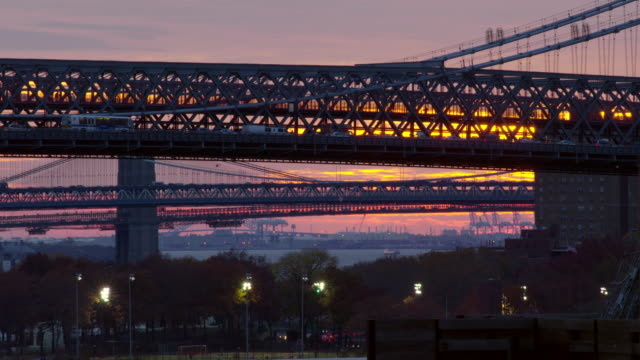 shot of traffic crossing the williamsburg bridge in new york city against a purple and pink sky. people play on a field in the bottom of the shot.  the manhattan bridge and the brooklyn bridge can be seen in the distance - williamsburg bridge stock videos and b-roll footage
