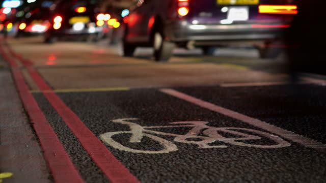 CU LA T/L Shot of Traffic defocused night time, red route and cycle lane road markings prominent / London, Greater London, United Kingdom