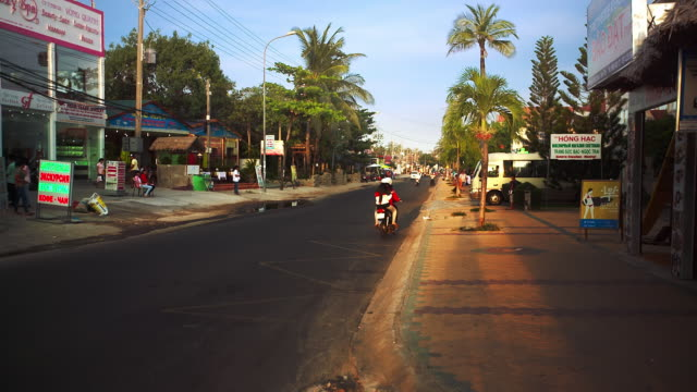 ms shot of traffic moves along street lined with palms and varied businesses, people pass by, blue sky / mui ne, vietnam - vietnam meridionale video stock e b–roll