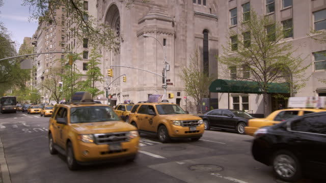 Shot of traffic moving down 5th Avenue in Manhattan near Central Park. In typical New York fashion a taxi speeds down the bus only lane