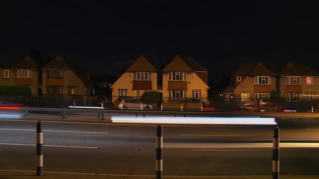 MS T/L Shot of Traffic moving down motorway past row of houses / London, United Kingdom