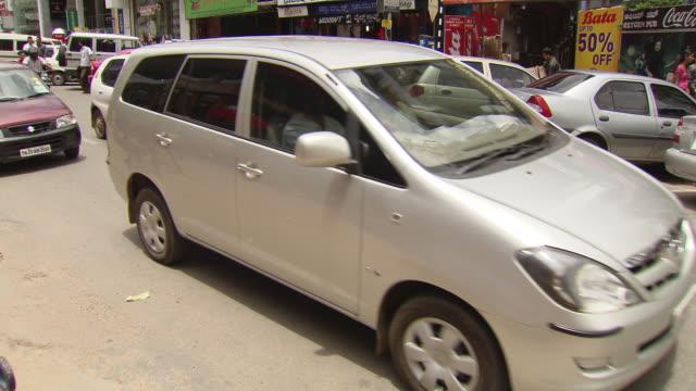 ms tu shot of traffic moving on city street along with shops / bangalore, india - 英字点の映像素材/bロール