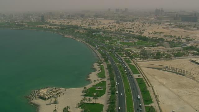 ms aerial shot of traffic moving on highway in city near ocean / qatar - qatar stock videos & royalty-free footage