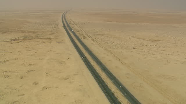 MS AERIAL PAN Shot of traffic moving on highway in open land at desert / Qatar