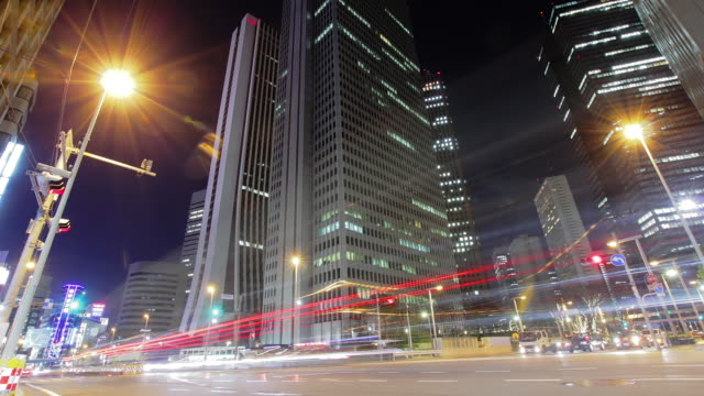 MS LA T/L Shot of traffic moving on road at night / shinjuku, Tokyo, Japan