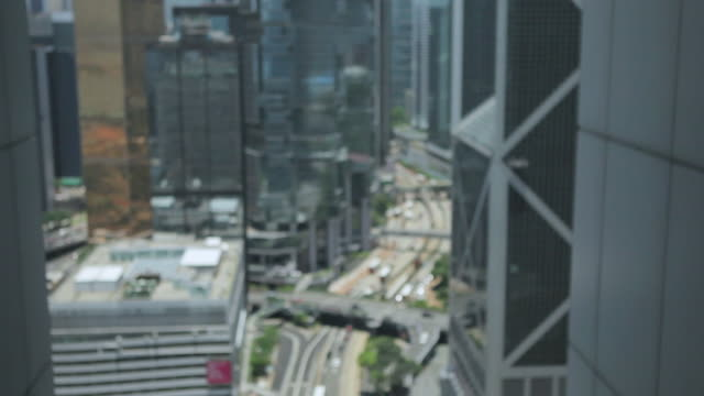 ms shot of traffic moving on road through skyscraper in city / hong kong, hong kong, hong kong - intoning bildbanksvideor och videomaterial från bakom kulisserna