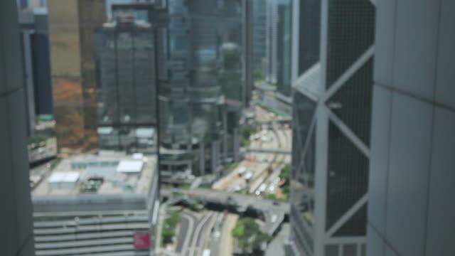 vídeos de stock, filmes e b-roll de ms shot of traffic moving on road through skyscraper in city / hong kong, hong kong, hong kong - sc47