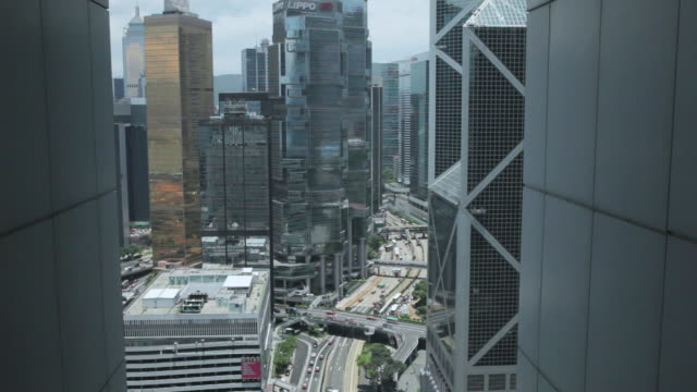 stockvideo's en b-roll-footage met ms r/f shot of traffic moving on road through skyscraper in city / hong kong, hong kong, hong kong - uitfaden