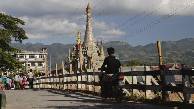 ms shot of traffic moving over bridge with silver pagoda / nyaungshwe, inle lake, shan state, myanmar - shan state stock videos & royalty-free footage
