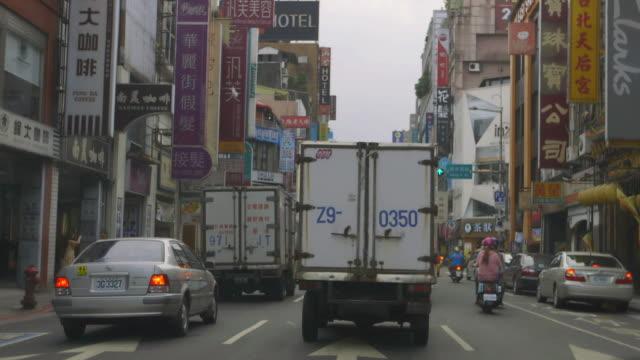 ms pov shot of traffic with shop signs all over low rise buildings either side of road / taipei, taiwan - butiksskylt bildbanksvideor och videomaterial från bakom kulisserna