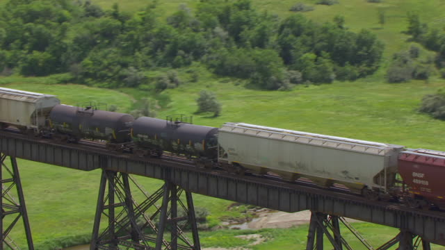 MS AERIAL TS Shot of Train cars traveling over Gasman Coulee Railroad Trestle / Minot, North Dakota, United States
