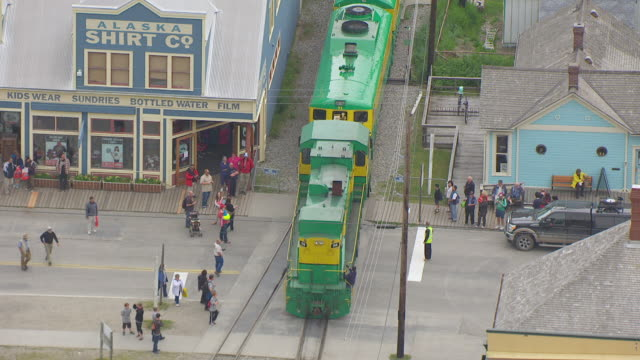 vídeos de stock, filmes e b-roll de cu aerial shot of train driving through downtown with people walking / skagway, alaska, united states - skagway