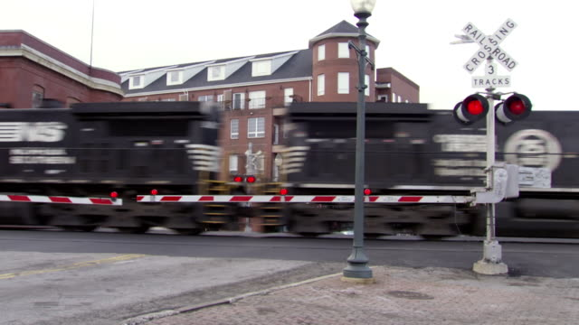 ms shot of train going by railroad crossing in center of city / greensboro, north carolina, united states - level crossing stock videos & royalty-free footage