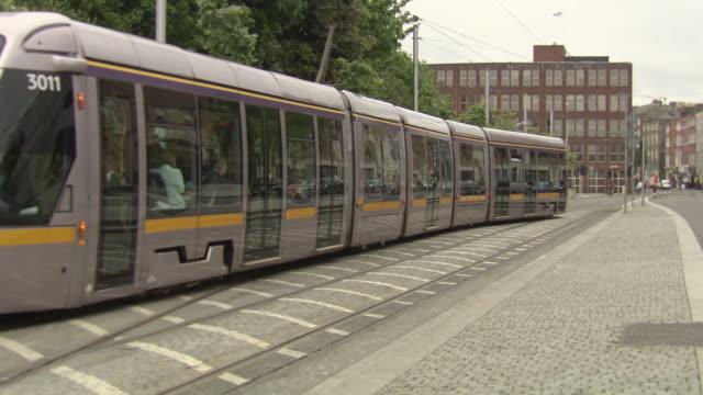 MS Shot of tram moving on street / Dublin, Ireland