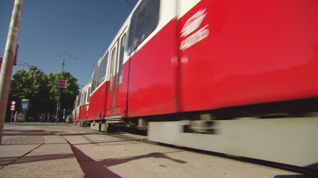 vídeos de stock e filmes b-roll de ms la shot of tram passing and traffic moving on street / vienna, austria - linha do elétrico