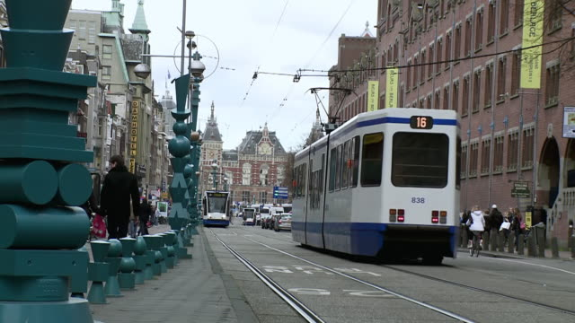stockvideo's en b-roll-footage met ms shot of trams moving along road and people walking around / amsterdam, holland - commercieel landvoertuig