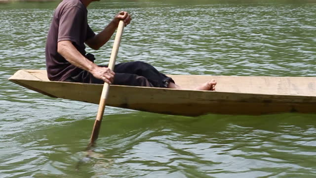 ms ts slo mo shot of travelling following man rowing wooden canoe with his hand holding paddle then tilt up again / ou river, luang prabang, laos - legs crossed at ankle stock videos and b-roll footage